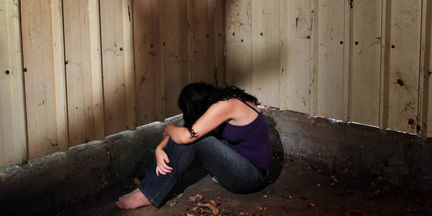 A woman who is a victim of abuse is hiding in the darkness of an old shed, sitting on the ground with a shadow of a mans hand hovering over her.   UPP / Reporters