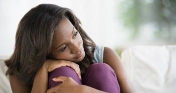 Black woman hugging her knees