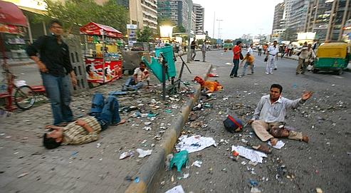 An injured man, right, shouts for help as others lie injured on a road after a bomb explosion in New Delhi, India, Saturday, Sept. 13, 2008. Witnesses say at least one explosion has hit a central New Delhi shopping area, leaving several people wounded.  (AP Photo/Mustafa Quraishi)