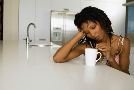 Bored Young Woman Stirring Coffee --- Image by © Vincent Mo/zefa/Corbis