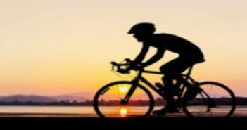 homme-faisant-un-cycle-au-temps-de-crpuscule-de-plage-59483512