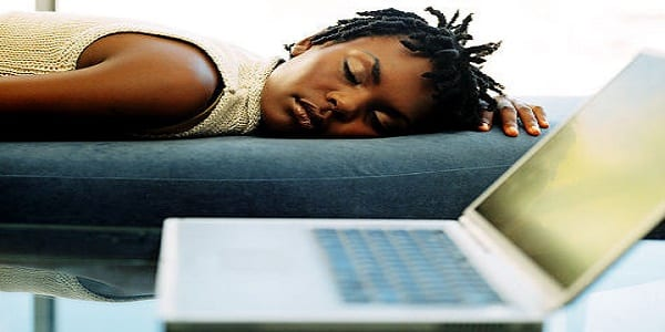 Young woman sleeping on a couch next to a laptop Original Filename: 57613069.jpg Gettyimages