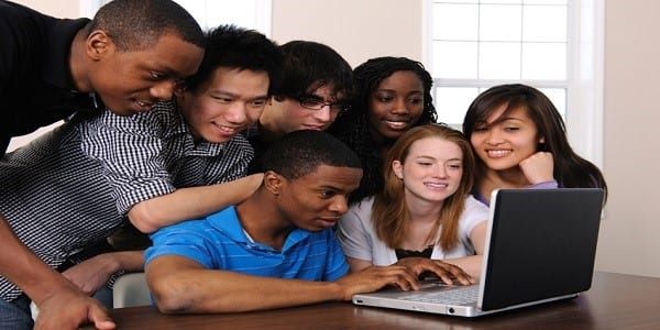 A group of college friends using a laptop.