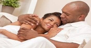 A happy African American man and woman couple in their thirties sitting at home together smiling and cuddling