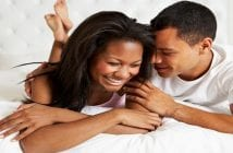 Couple Relaxing In Bed Wearing Pajamas