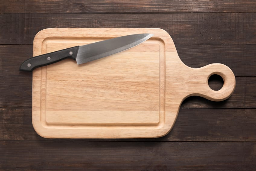 Knife and cutting board on the wooden background
