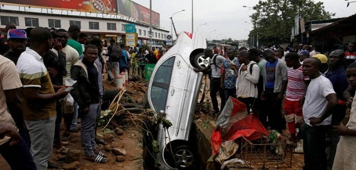 People look at a car in a sewer after a flood in Abidjan