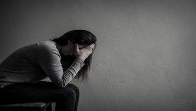 femme-deprimee-assise-chaise-dans-piece-sombre-maison_53476-2193
