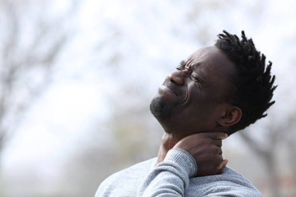 Black man suffering neck ache complaining outdoors