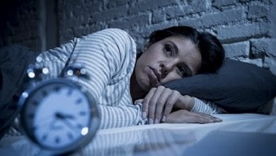 woman in bed late night trying to sleep suffering insomnia